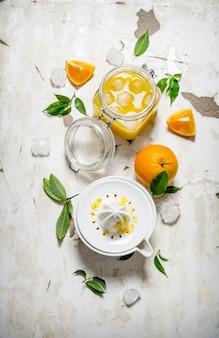 신선한 오렌지 주스와 얼음, 오렌지 조각과 과즙 짜는기구. 소박한 테이블에. 평면도