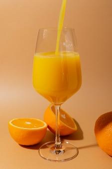 ベージュのワイングラスに果肉入りのフレッシュオレンジジュース