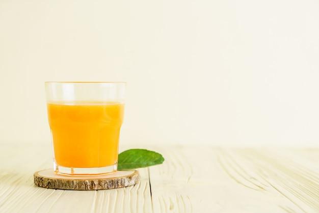Fresh orange juice on wood background