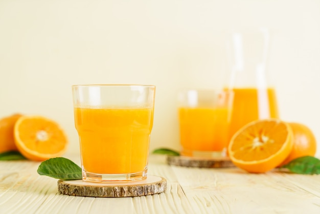 Fresh orange juice on wood background