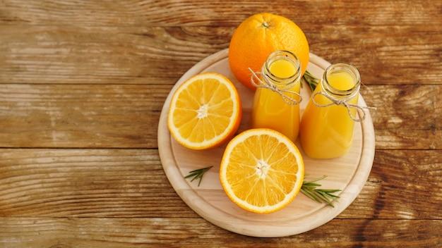 Fresh orange juice on wooden table on a wooden board