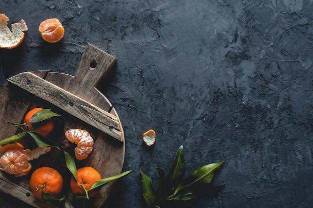 木製のまな板に新鮮なオレンジみかん。エコベジタリアン。 pnov2019