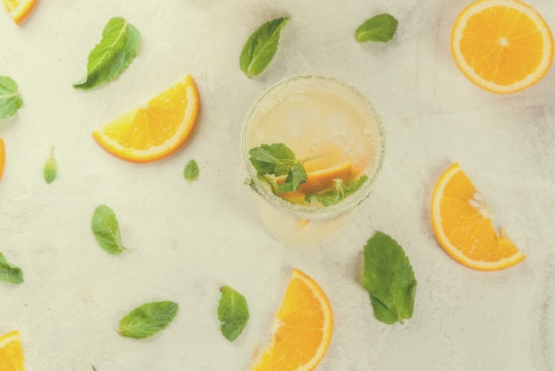 Fresh orange and mint lemonade with ice in glasses on light grey stone marble table top view