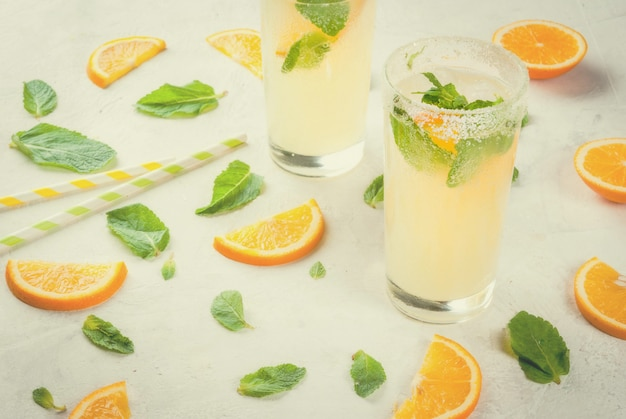 Fresh orange and mint lemonade with ice in glasses on light grey stone marble table