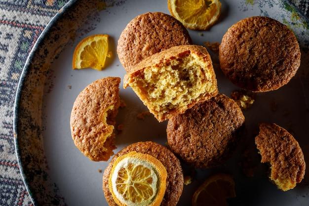Свежие апельсиновые кексы на круглой тарелке.