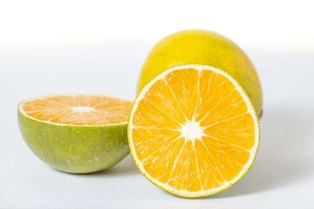 白い背景で隔離のジュースの新鮮なオレンジ。ナチュラルでオーガニック