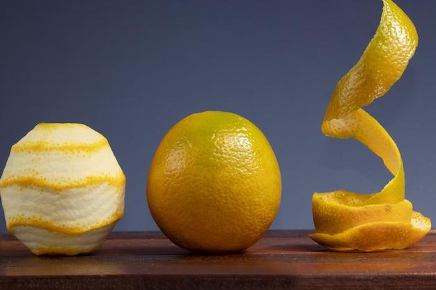 Fresh orange and peeled fruit on wooden table.