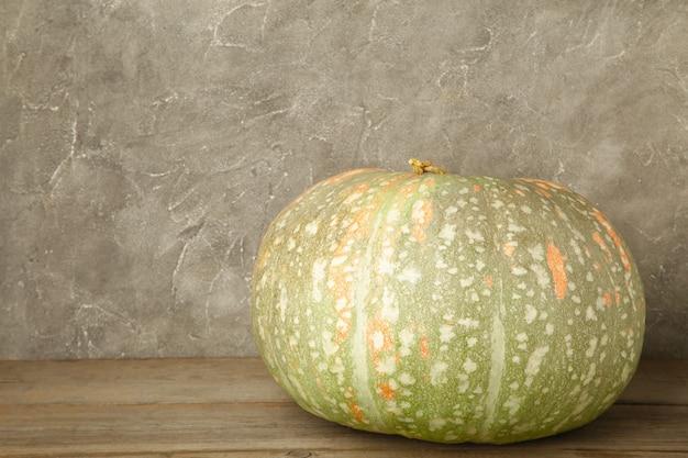 Fresh orange pumpkin on grey concrete background. top view