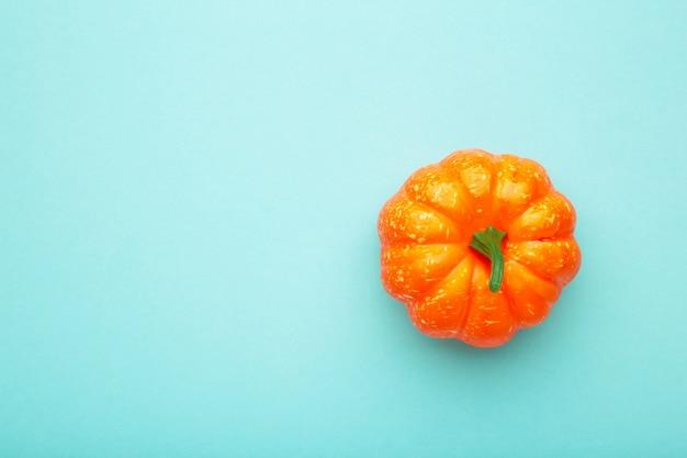 青いパステル背景に新鮮なオレンジ色のカボチャ