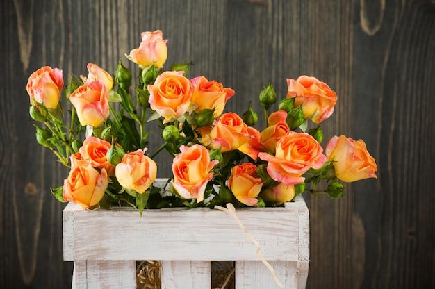 소박한 상자에 신선한 오렌지 장미 꽃