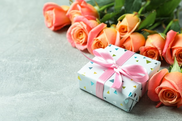 Fresh orange roses with gift, closeup