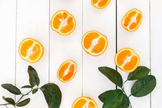 白い木製のテーブルの上の新鮮なオレンジスライス