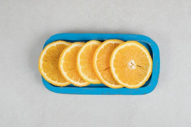 파란색 접시에 신선한 오렌지 조각