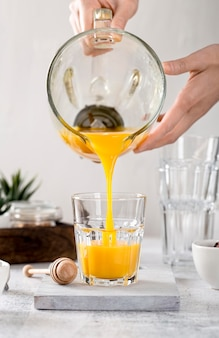 Fresh orange smoothie being poured in a glass