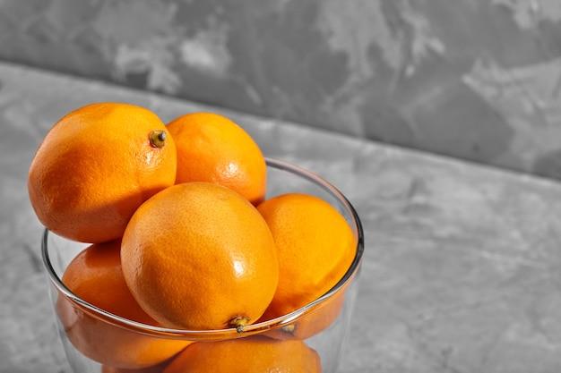 コンクリートの背景に新鮮なオレンジ色のタシケントレモンまたはマイヤーレモン。ビタミンc。