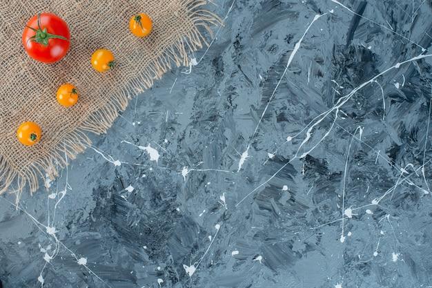 大理石の背景に、黄麻布のナプキンに新鮮なオレンジトマトと赤いトマト。