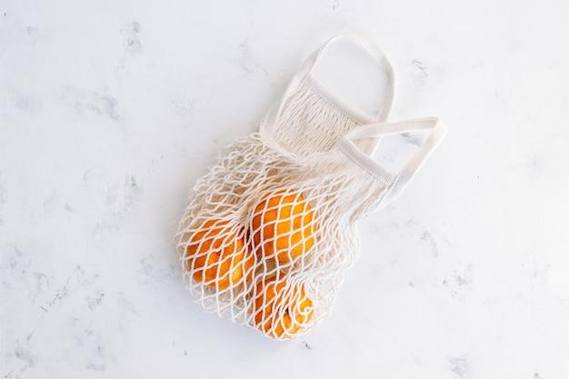 Fresh oranges in eco net shopping bag on white background.