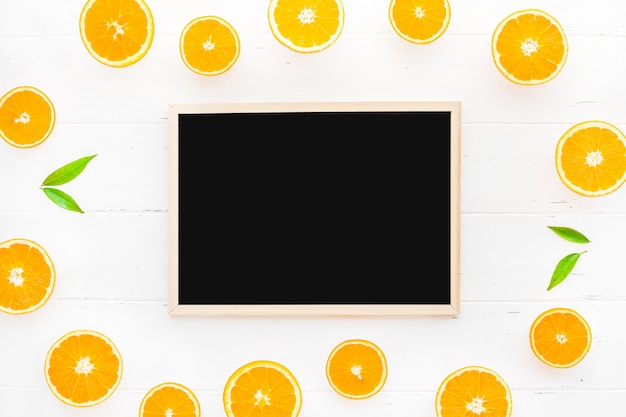 Fresh oranges frame with blackboard on white background