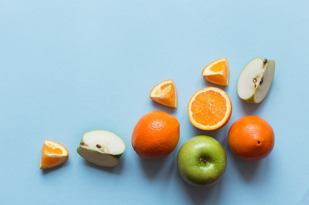Fresh oranges and green apples on the blue surface