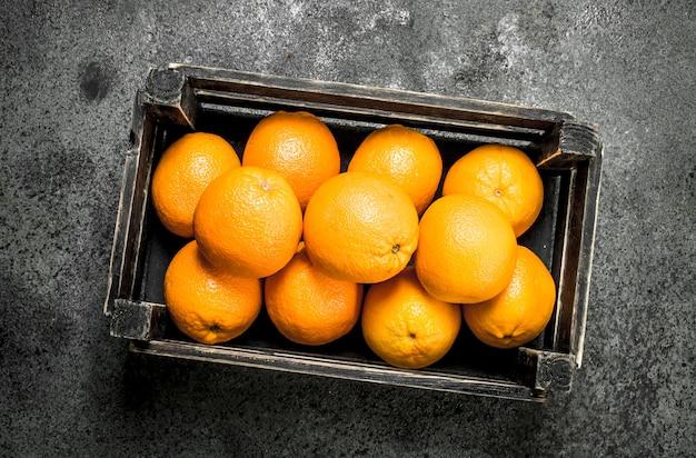 Свежие апельсины в коробке на деревенском фоне
