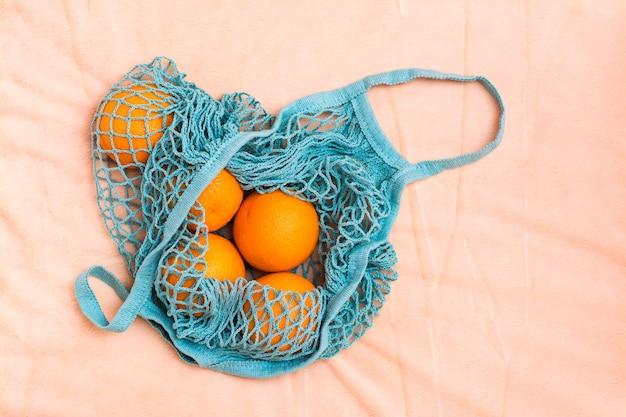 직물에 메쉬 가방에 신선한 오렌지. 제로 폐기물 개념