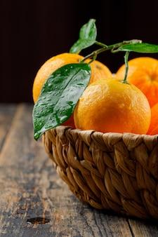 Свежие апельсины в плетеной корзине с боковым видом на черный и деревянный стол