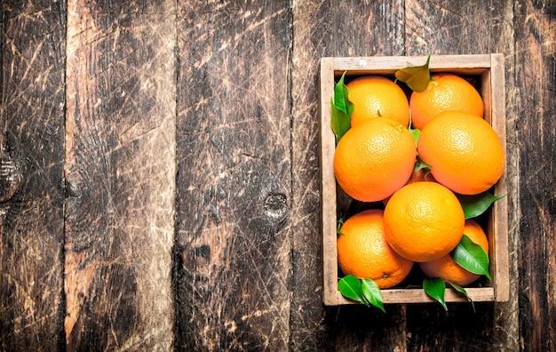 古い箱に入った新鮮なオレンジ。木製の背景に。