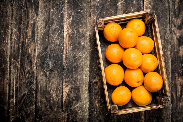 Свежие апельсины в коробке на деревянном фоне
