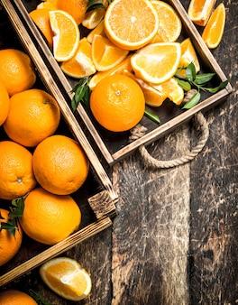 Свежие апельсины в коробках на деревянном фоне