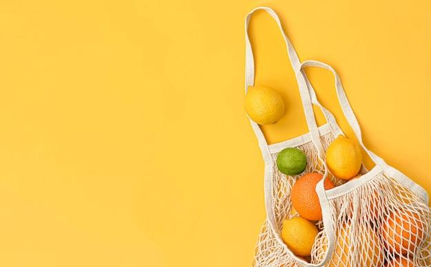 노란색 배경에 메쉬 가방에 신선한 오렌지, 레몬, 라임, 자몽