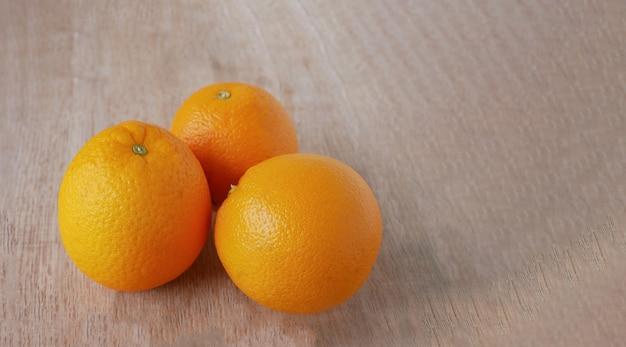 Fresh oranges on natural wood background