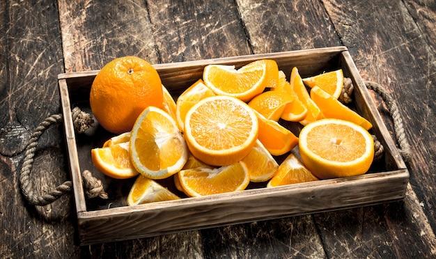 トレイに新鮮なオレンジ。木の表面に。