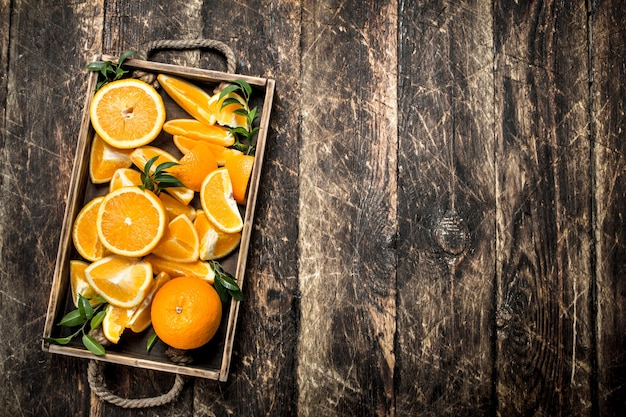 木製のテーブルのトレイに新鮮なオレンジ。