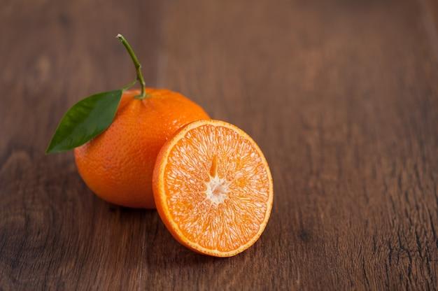 茶色の木製のテーブルに新鮮なオレンジ