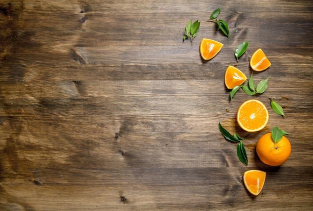 新鮮なオレンジ全体、カット、葉。