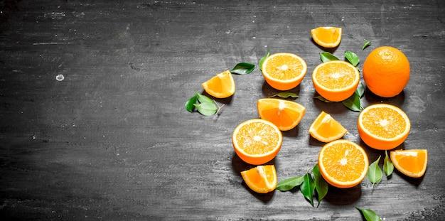 黒い黒板に緑の葉と新鮮なオレンジ