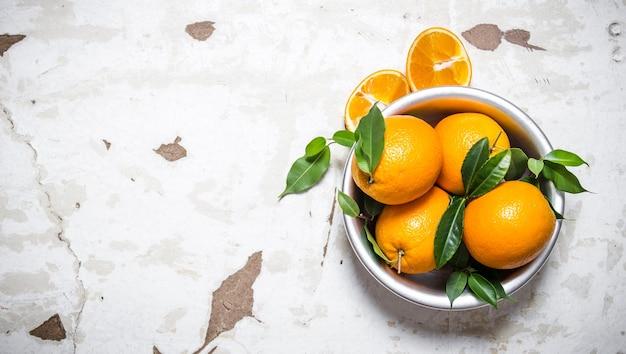 ボウルに葉が付いている新鮮なオレンジ。