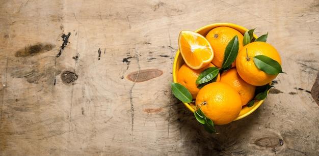 カップの葉と新鮮なオレンジ。
