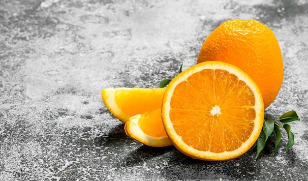 Свежие апельсины с листьями на деревенском фоне