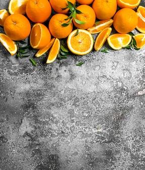 Свежие апельсины с листьями. на деревенском фоне.