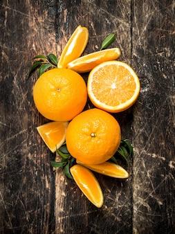 Свежие апельсины с листьями на деревянном фоне