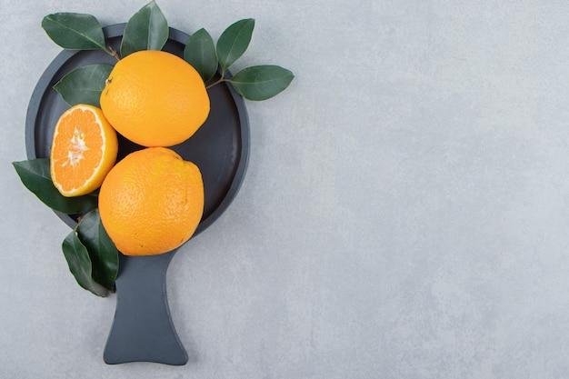 Свежие апельсины с листьями на черной разделочной доске.