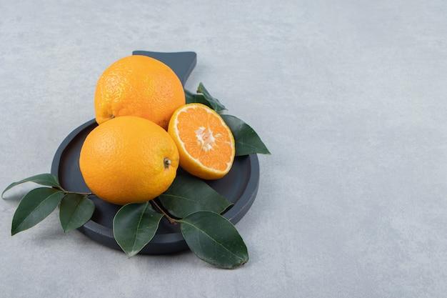 Свежие апельсины с листьями на черной разделочной доске