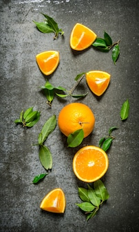 Fresh oranges with leaves. on the stone table. top view