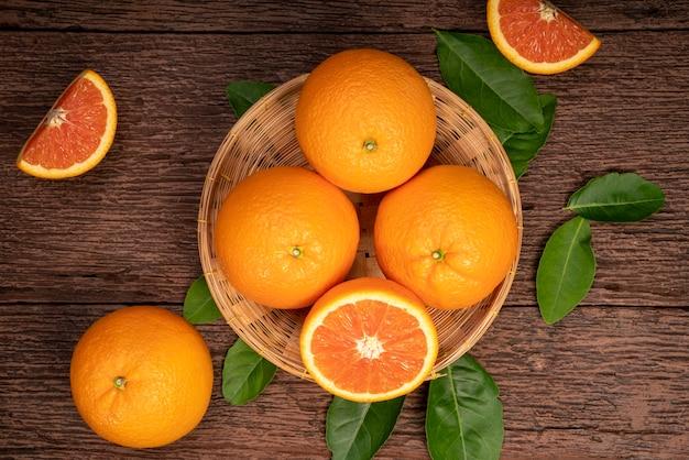 Свежие апельсины с апельсинами дольки с листьями