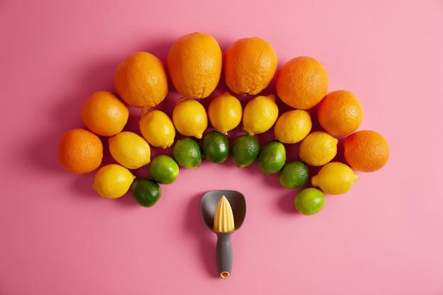 手動ジューサーの上に半円形に配置された新鮮なオレンジ、黄色のレモン、緑のライム。柑橘系の果物から有機ジュースを調製するために使用される絞り器。ビタミンと健康的なライフスタイルの概念。