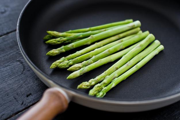 Fresh organic asparagus in a frying pan.
