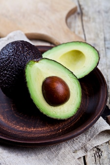 Fresh organic avocado on ceramic plate and linen napkin on rustic wooden table