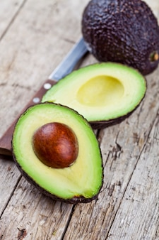 Fresh organic avocado and knife on old wooden table