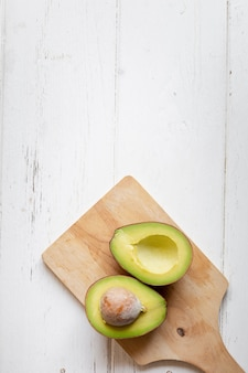 Fresh organic avocado sliced in half on white wooden table